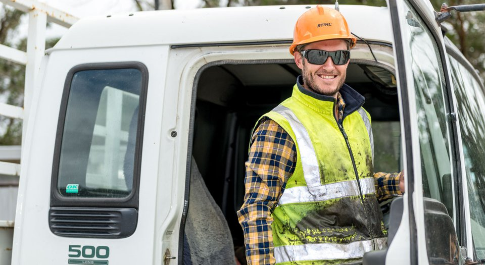 Construction worker smiles at camera from truck.jpg