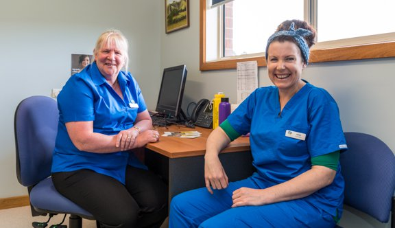 Nurses smile at camera at desk photo.jpg