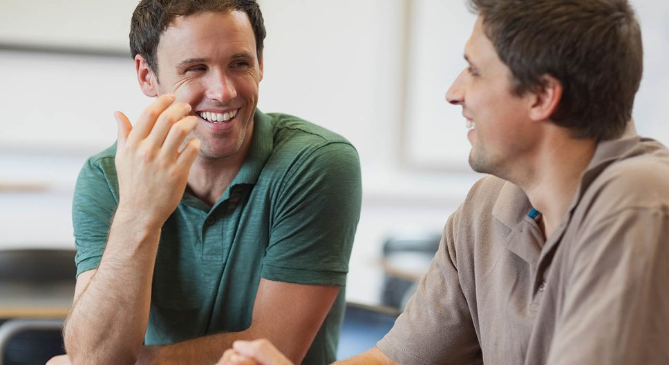 Two friends laugh together at a table.jpg