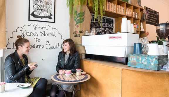 Two women holding coffee laughing in cafe photo.jpg