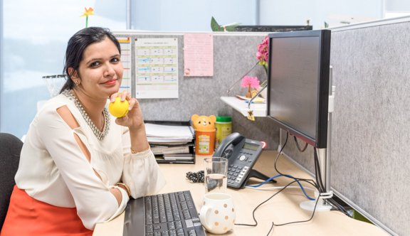 Woman holds stressball smiling at desk photo.jpg