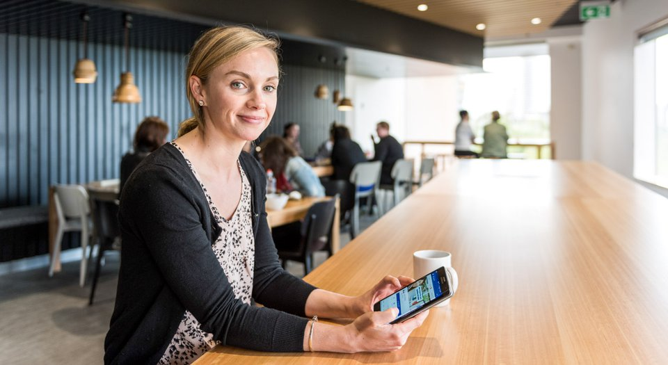 Woman smiles at camera while looking at Quit Facebook page.jpg