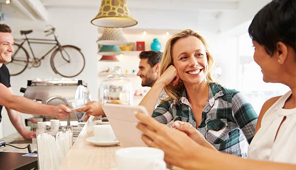 Woman smiles at friend in cafe photo.jpg