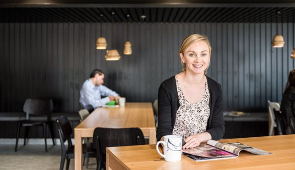 Woman smiles from magazine at cafeteria photo.jpg